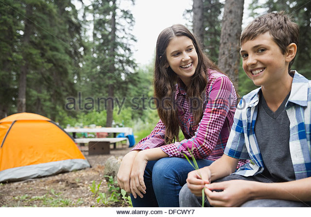 Portrait of boy sitting with sister at campsite - Stock Image