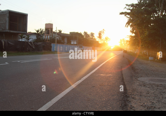 Sun shining on rural road - Stock Image