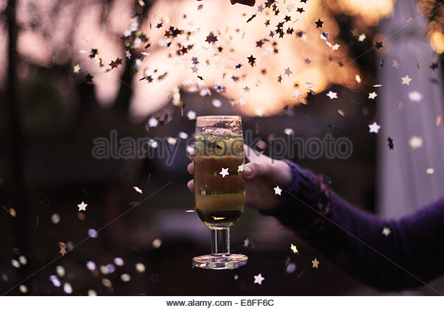 Woman's Hand holding cocktail during New Year's Eve celebration - Stock Image