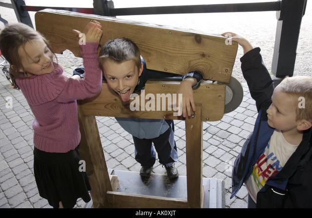 England UK Alnwick Castle Harry Potter movie site stocks pillory boy girl - Stock Image