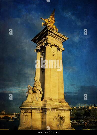 Gilt-bronze statue of a Fame restraining Pegasus watches over the Pont Alexandre III bridge, supported on massive - Stock Image