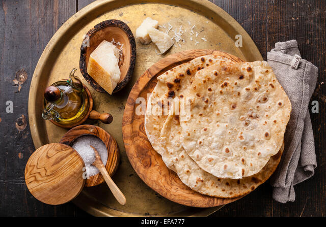 Fried tortilla with cheese on olive wood plate on metal background - Stock Image