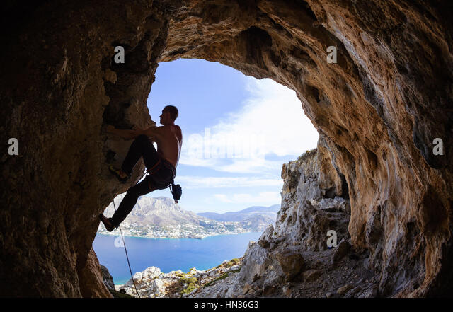 Young man climbing along rocks - Stock Image