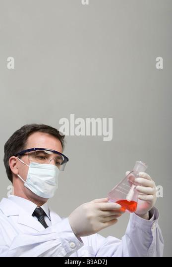 Scientist examining liquid in beaker - Stock Image