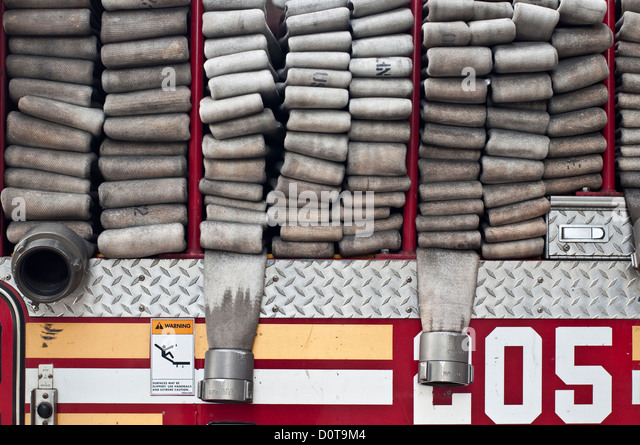 Hoses neatly loaded in the back of a FDNY firetruck in Brooklyn, NYC. - Stock Image