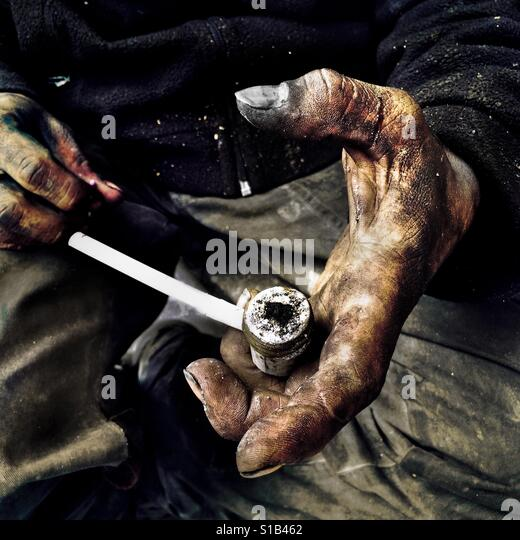 A Colombian ?basuco? smoker, living on the street, shows an improvised pipe loaded by raw cocaine paste, in Bogota, - Stock-Bilder