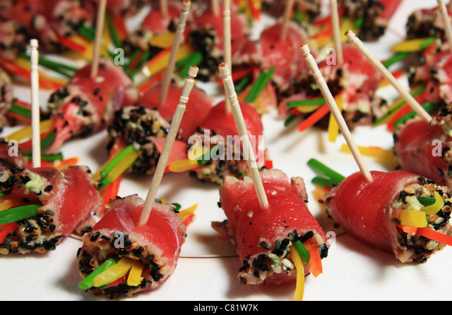 a plate of rolled tuna sushi held on toothpicks - Stock Image