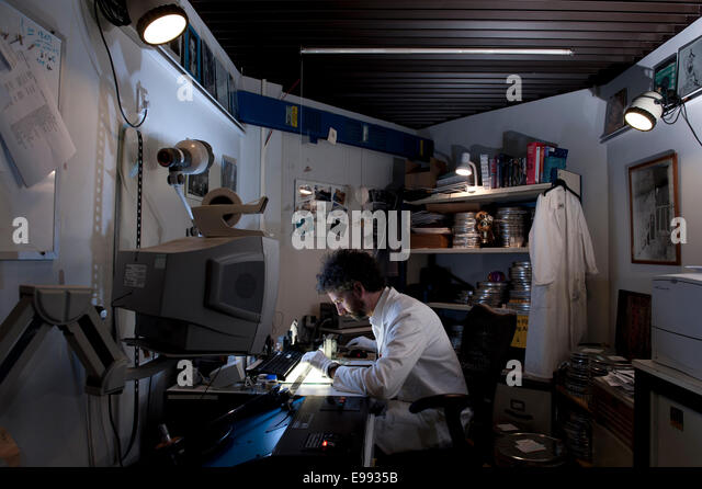 portrait of technical member of staff at the BFI archive with white lab coat, film reels & movie archival equipment - Stock Image