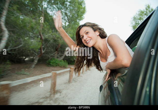 Young woman waving from car window - Stock Image