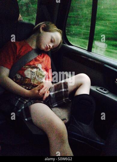Boy sleeping in car during road trip - Stock Image