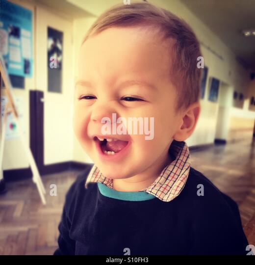 Happy baby boy laughing, having a great time in school - Stock Image