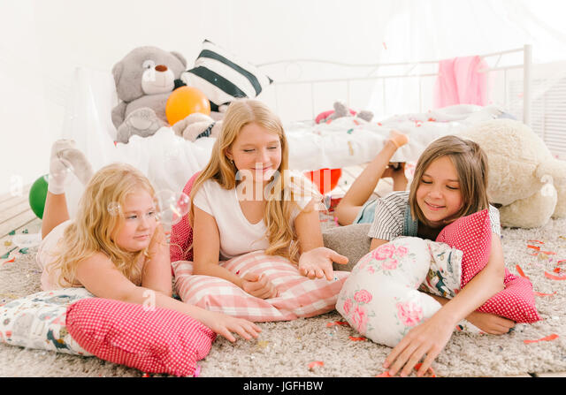 Smiling Middle Eastern girls laying on floor watching bubbles - Stock Image