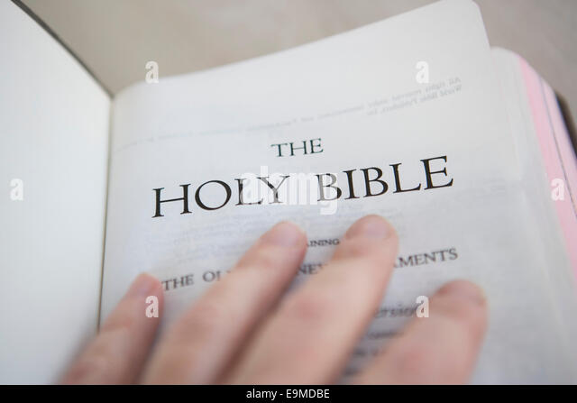 Person holding an open Bible - Stock-Bilder