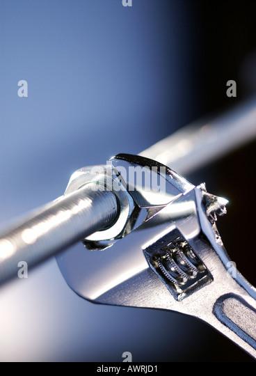 Wrench locked onto nut, close-up - Stock Image