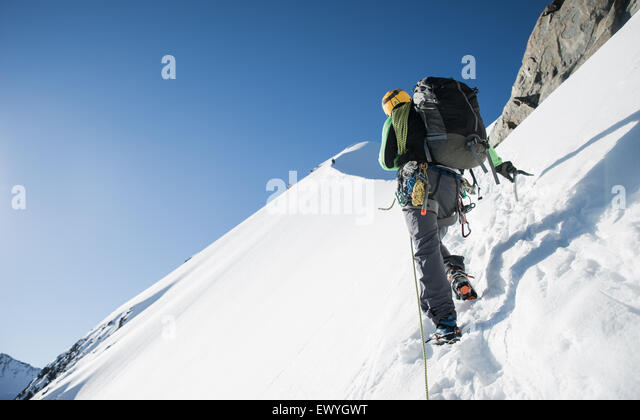 Man mountain climbing at Bianco Ridge, Swiss Alps, Bernina region, Switzerland - Stock Image