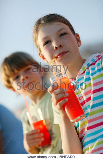 Girl and boy with fruit Juice, Formentera, Balearic Islands, Spain - Stock Image