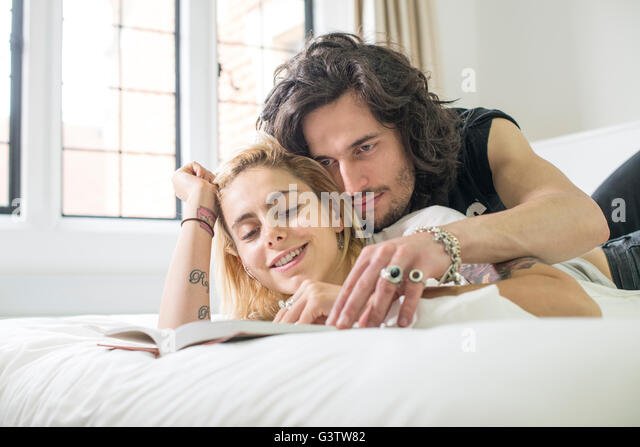 A cool young couple lying on a bed looking at a book. - Stock Image