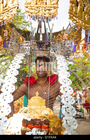 A Hindu devotee carrying portable shrine during Thaipusam in Singapore, Southeast Asia, Asia - Stock Image