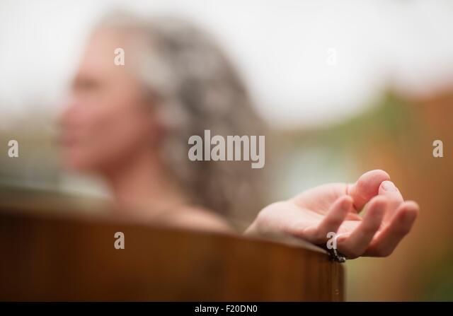 Hand of mature woman meditating in hot tub at eco retreat - Stock Image