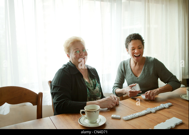 Mother and adult daughter playing dominoes - Stock-Bilder