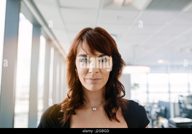 Close up portrait of beautiful mature businesswoman standing in office. Caucasian female corporate professional - Stock Image