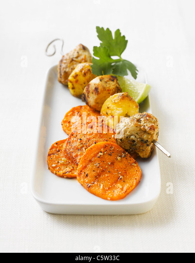 Turkey hen skewers with mango and sweet potato slices on platter - Stock Image