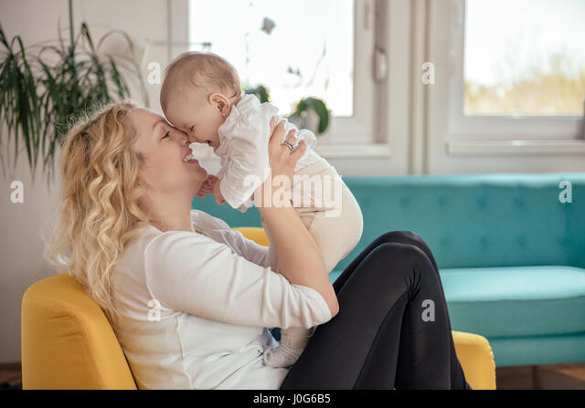 Mother and her baby head to head sitting at yellow armchair - Stock Image