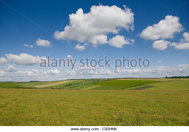 Clouds in blue sky over sunny rural fields - Stock Image