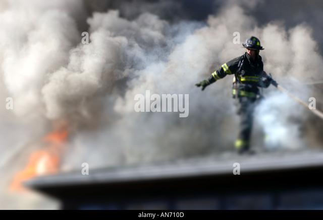 Firefighter on a roof fighting a fire - Stock-Bilder