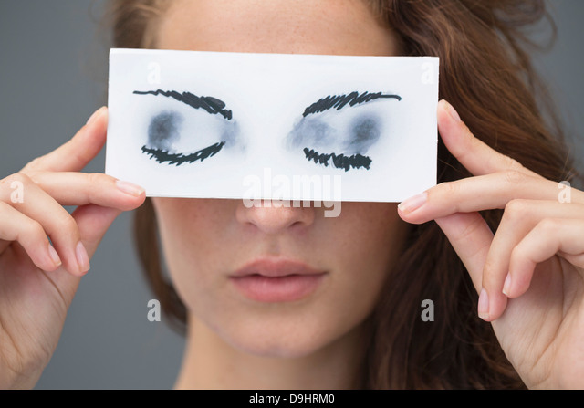 Woman holding a paper with false eyes in front of her face - Stock Image