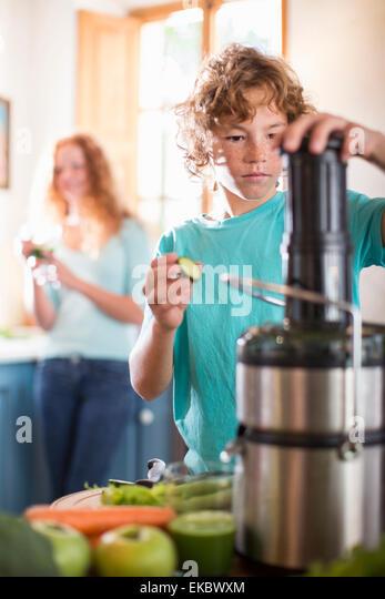 Teenage boy blending fruit in kitchen - Stock-Bilder