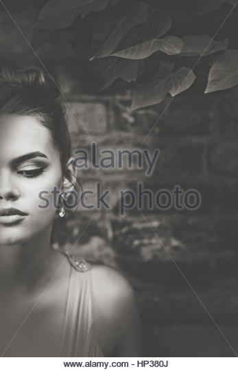 Beautiful young woman  in front of a brick wall - Stock Image