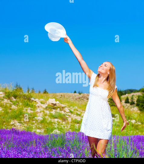 Cute girl dancing on lavender field, beautiful happy woman enjoying purple floral glade, pretty cheerful young lady - Stock Image