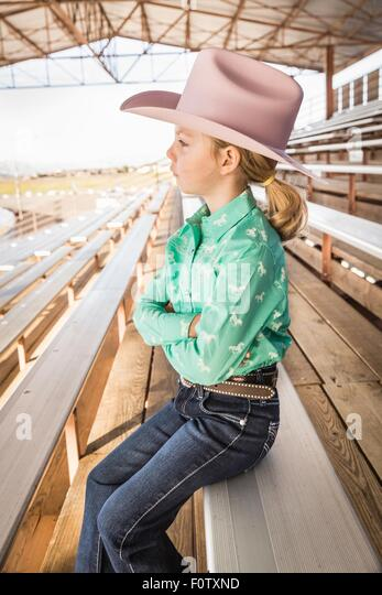 Girl wearing cowboy hat on bench with arms folded, portrait - Stock Image