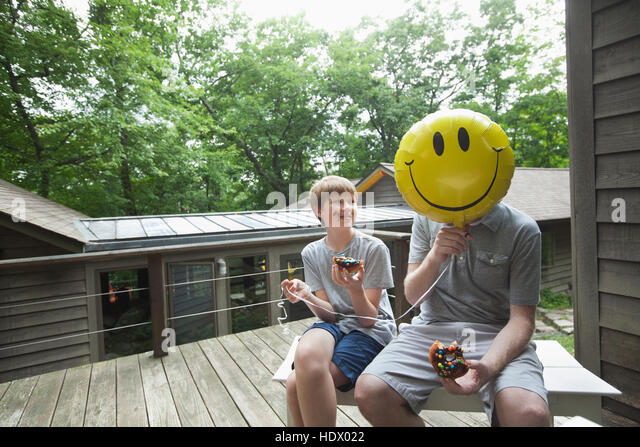 Caucasian father and son eating donuts with smiley face balloon - Stock Image