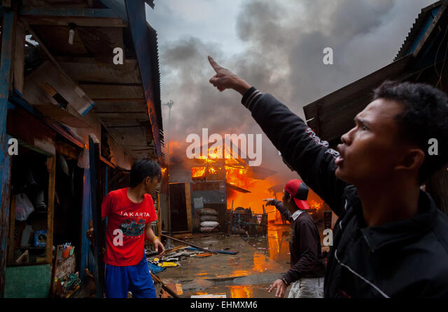 Local people coordinate to fight a fire accident in the dense Jakarta neighborhood. © Reynold Sumayku - Stock Image