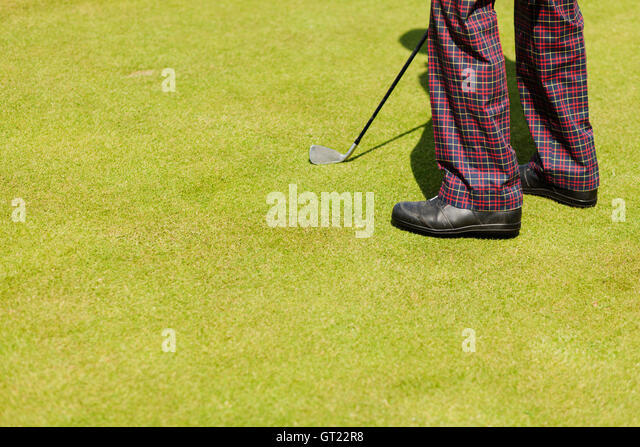 Low section of man with golf club on field - Stock-Bilder