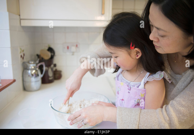 Mother and daughter in kitchen, mixing ingredients in bowl - Stock-Bilder
