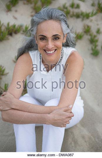 Portrait of mature woman sitting on beach - Stock Image