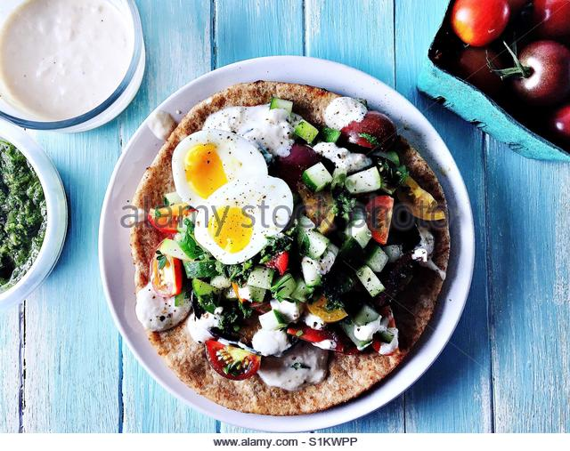 Sabih with sous vide soft boiled egg on white plate on blue wood board background with basket of cherry tomatoes, - Stock Image