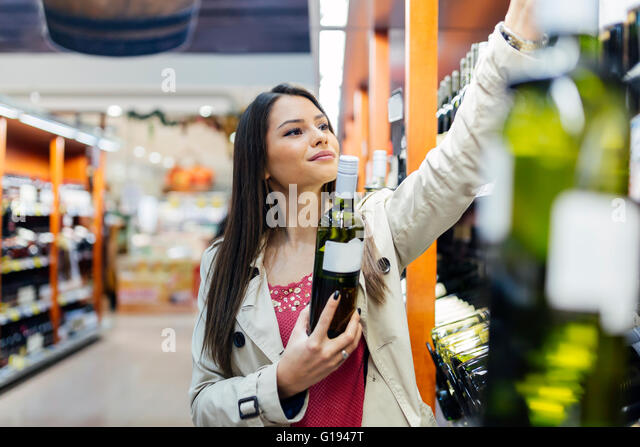 Woman deciding what wine to buy and shopping in supermarket - Stock Image
