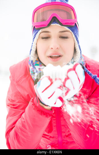 Young woman wearing winter coat blowing snow outdoors - Stock Image