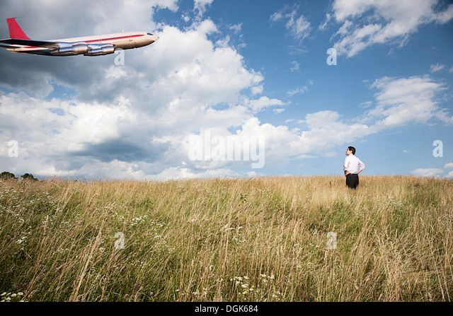 Businessman in field looking at airplane - Stock Image
