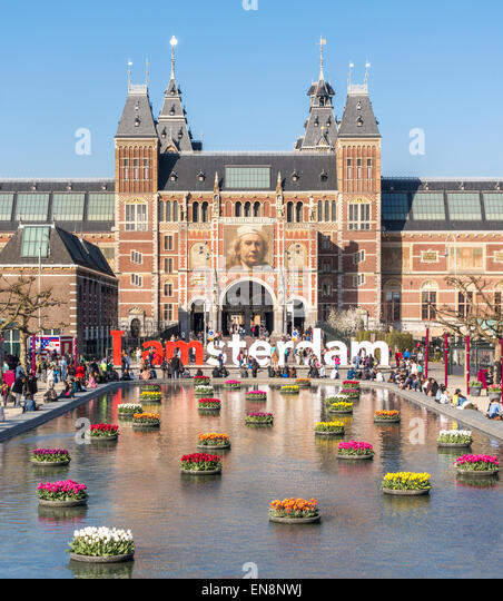 Rijksmuseum Amsterdam Rijksmuseum National Museum with I Amsterdam sign IAmsterdam and tulips in the reflecting - Stock Image
