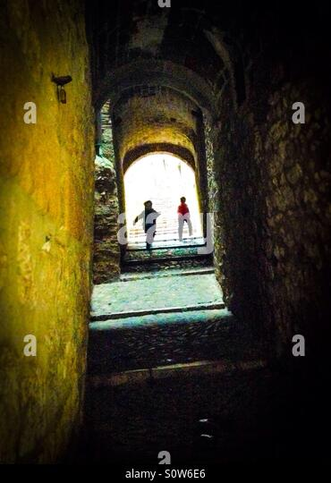 Two silhouettes walking through a dark alley in the Call (jewish quarter), Girona, Catalonia - Stock Image