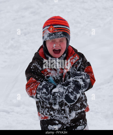 A young boy (3 yrs old0 crying after falling into snow - Stock Image