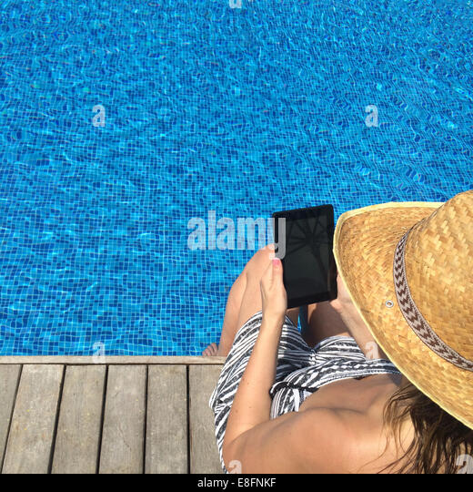 Woman with digital tablet sitting at the edge of swimming pool - Stock Image