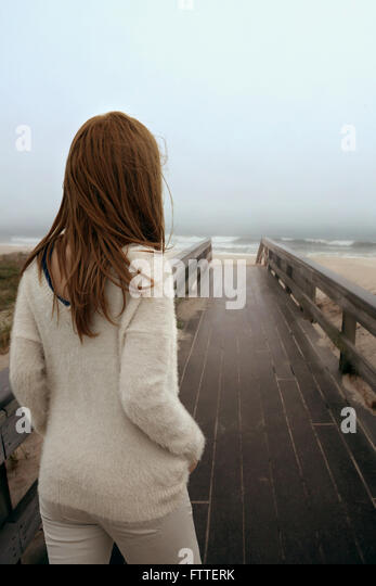 Woman walking on wooden boardwalk at beach - Stock Image