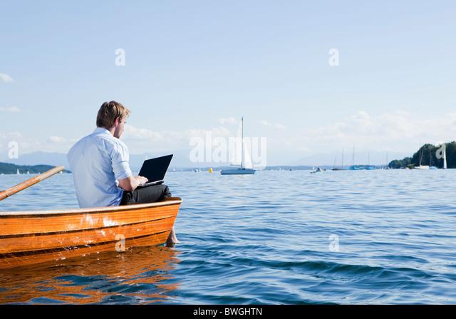 Man sitting on a rowboat using laptob - Stock Image