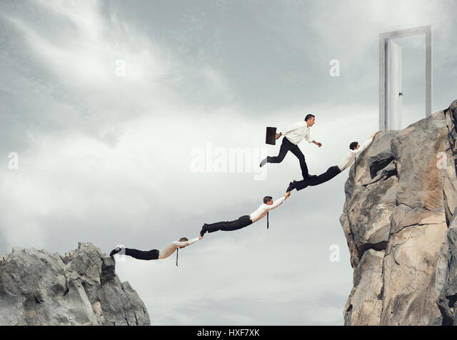 Businessmen working together to reach a door - Stock Image